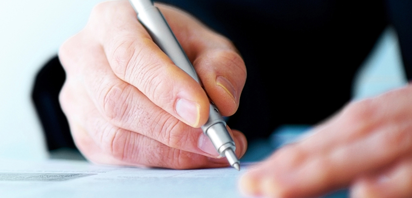 Business man hand writing on paper – Copyspace